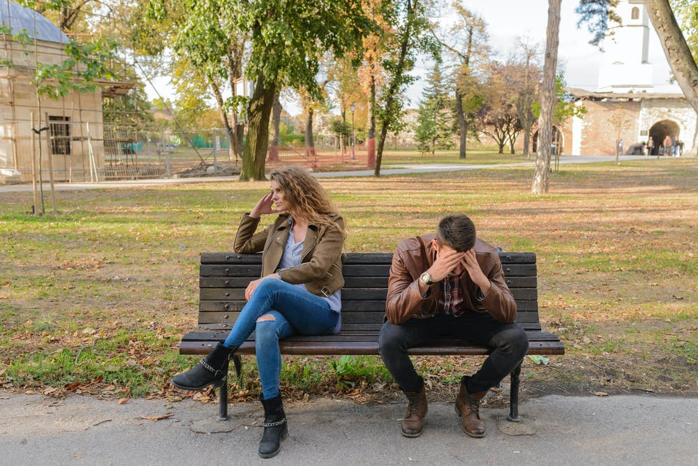 Man and woman sitting on a bench. | Photo: Pexels