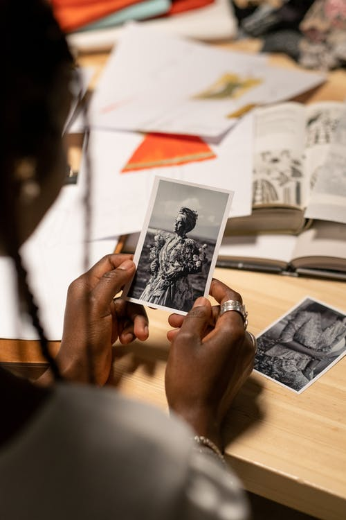 Fashion Designer Holding and Looking at Photo