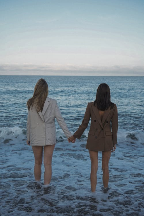 Women Standing in Water Holding Hands and Wearing Jackets Backwards