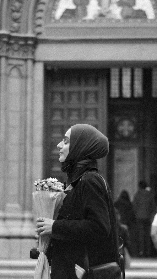 Woman With Scarf on Head Holding Flowers