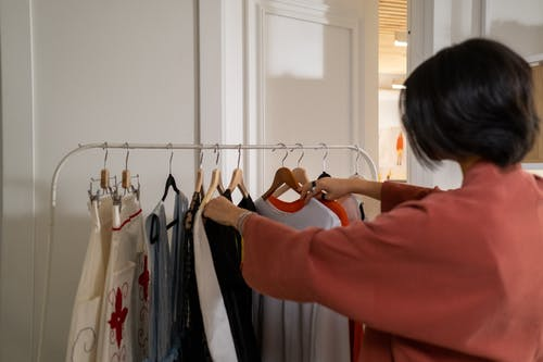Rear View on Woman Checking Clothes on Rack