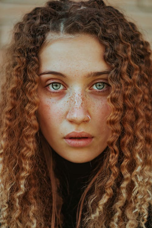 Girl with Curly, Ginger Hair Looking at Camera