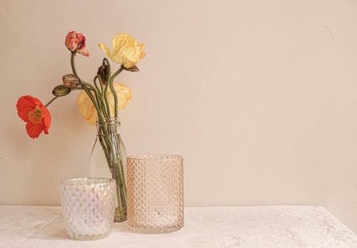 Yellow and Red Roses in White Ceramic Vase Beside White Ceramic Vase