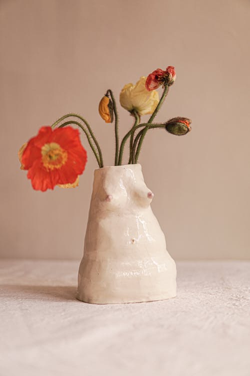 Red and Yellow Flowers in White Ceramic Vase