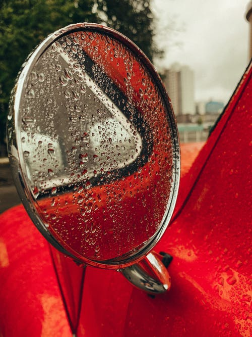 Red Car Side Mirror With Water Droplets