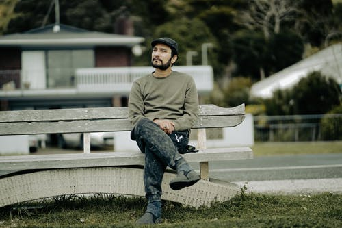 Man in Gray Sweater and Blue Denim Jeans Sitting on Bench