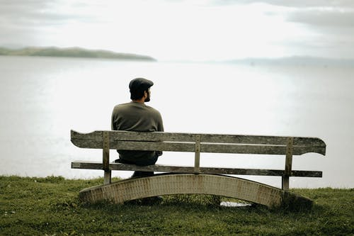 Man in Gray Shirt Sitting on Brown Wooden Bench