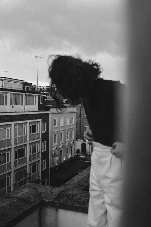 Grayscale Photo of Woman in White Dress Shirt Standing Near Building