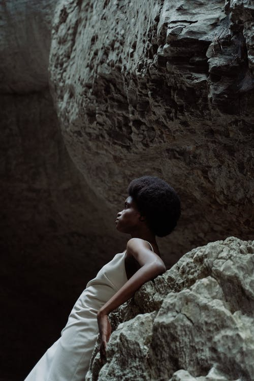 Woman in White Sleeveless Dress Sitting on Rock