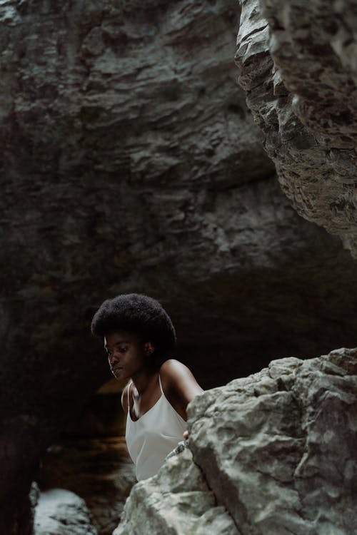 Woman in White Tank Top Standing Near Brown Rock