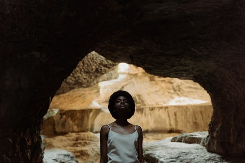 Woman in White Tank Top Standing in Cave