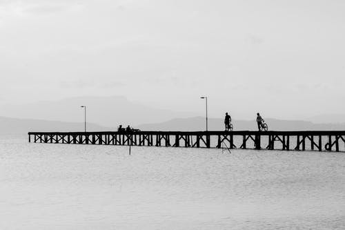 Grayscale Photo of People Standing on Dock