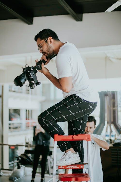 Photographer on Ladder Working