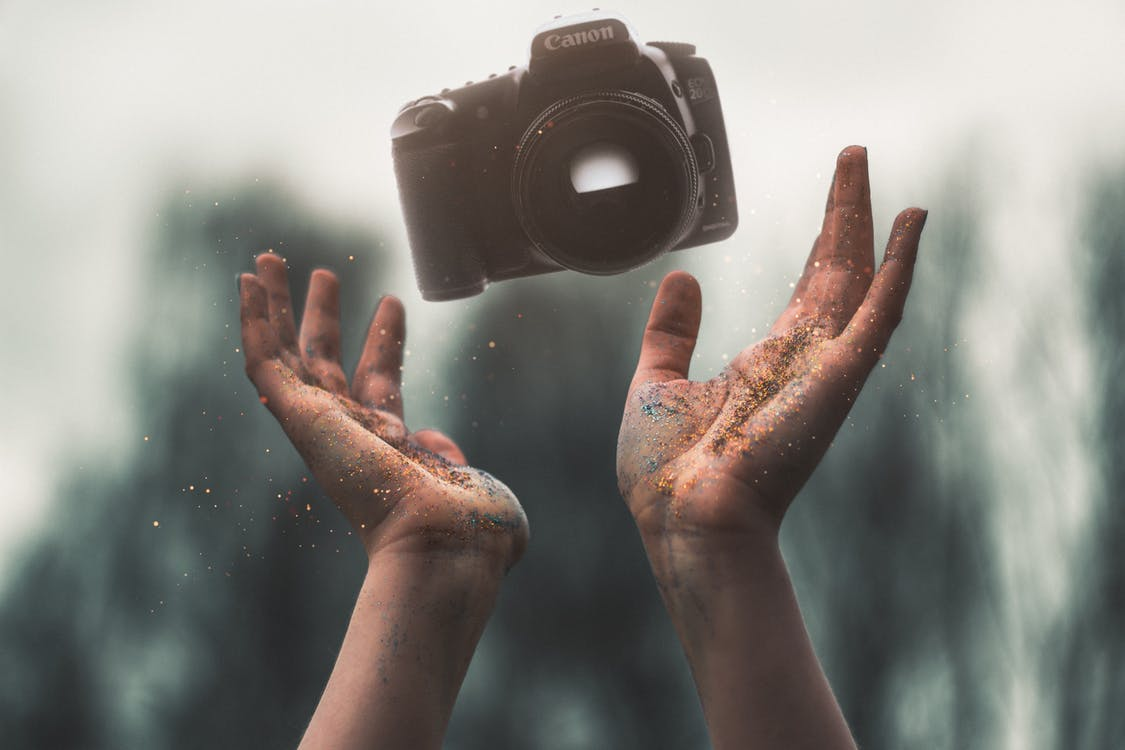 Selevtice Photography of Black Canon Dslr Camera Above Human Hands