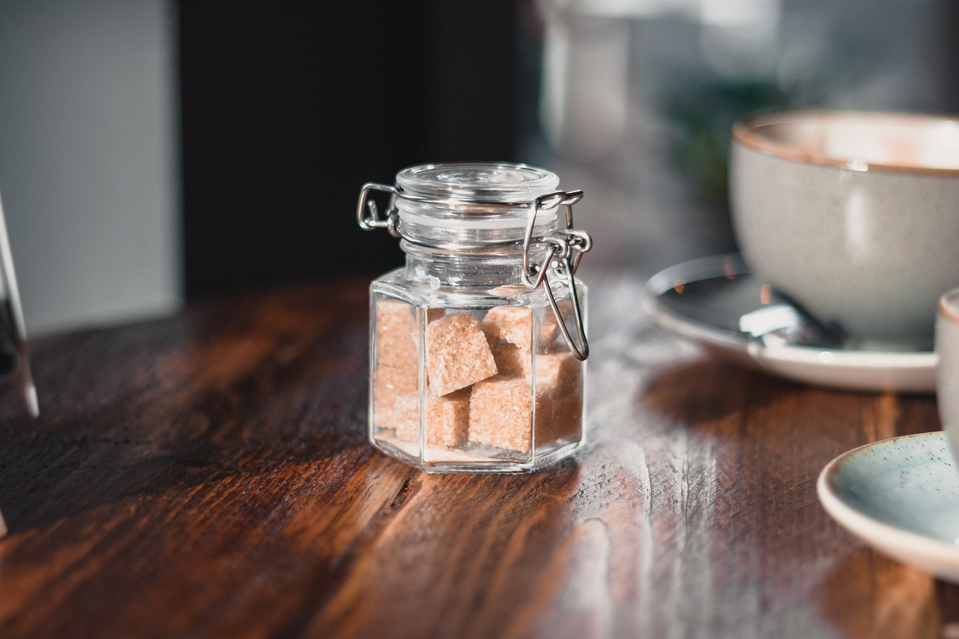 Clear Condiment Shaker With Brown Sugar Cubes Near Gray Teacup