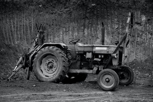 Grayscale Photo of Tractor Near Tree