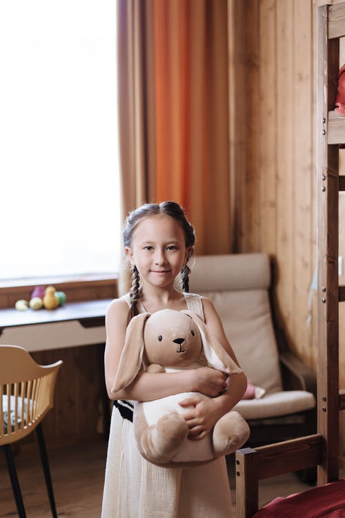 A Little Girl Looking At Camera and Holding a Stuffed Toy