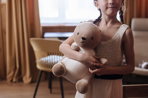 A Little Girl Hugging a Stuffed Toy