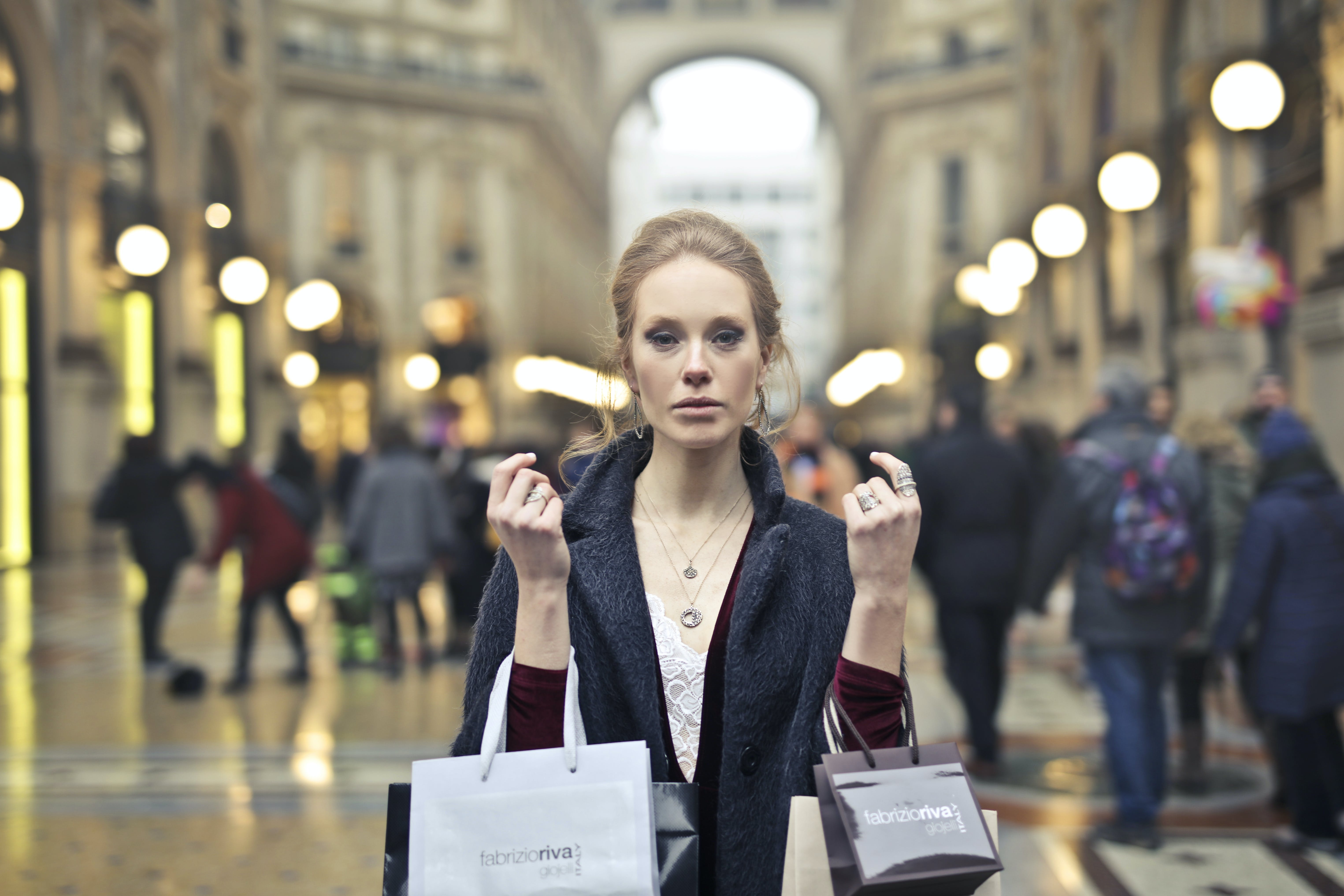 Woman Wearing Black Coat Holding Assorted-color Shopping Bags on Building
