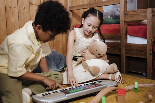 Brother and Sister Playing With Synthesizer