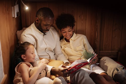Father With Mother Reading Book to Daughter