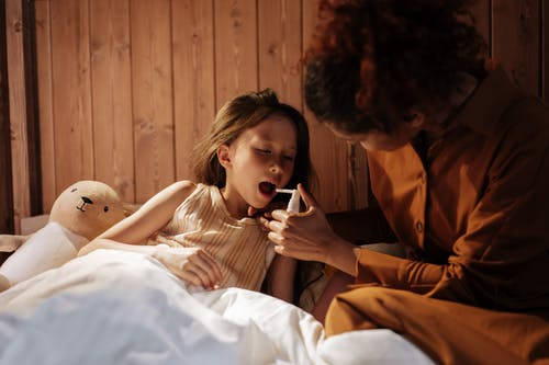 Mother Giving Her Daughter Medical Treatment for Flu Before Bedtime