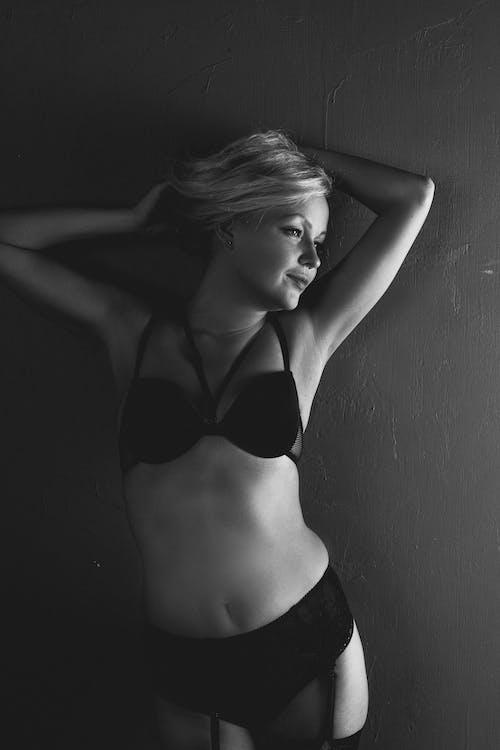 Woman in Black Brassiere Leaning on Wall