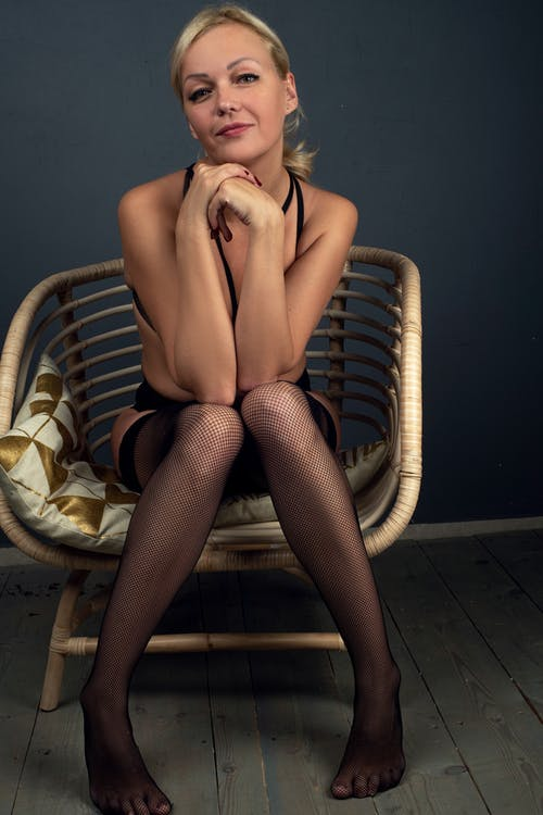 Nude Woman Sitting on Brown and White Striped Armchair