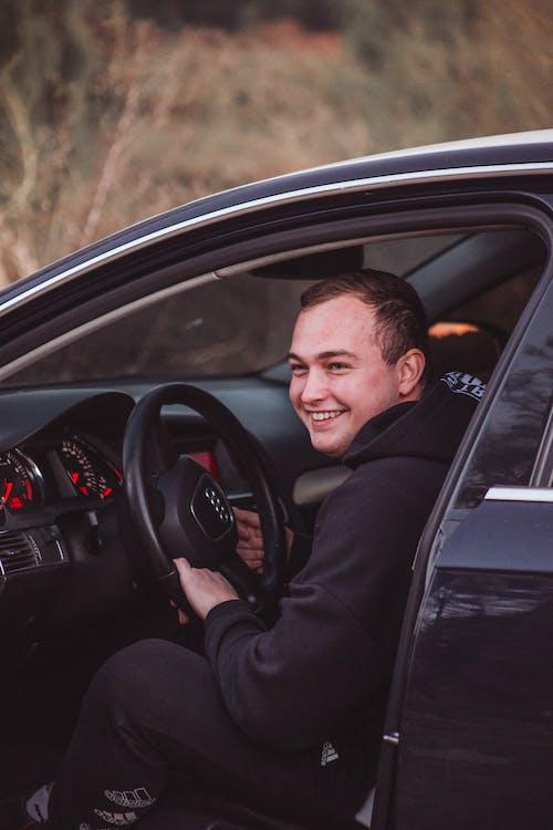 Man in Sweatshirt Sitting in Car