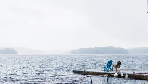 Empty chairs on pier on foggy day