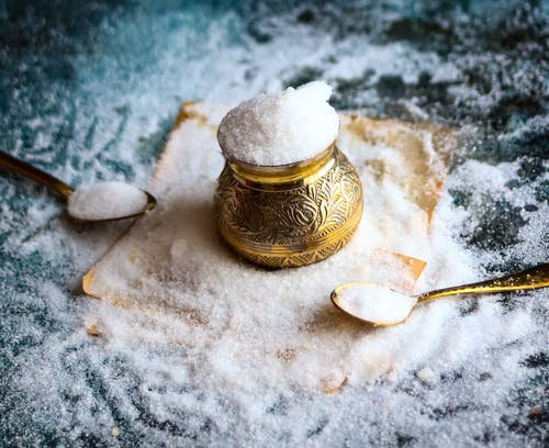 Gold and White Ceramic Jar on White Textile