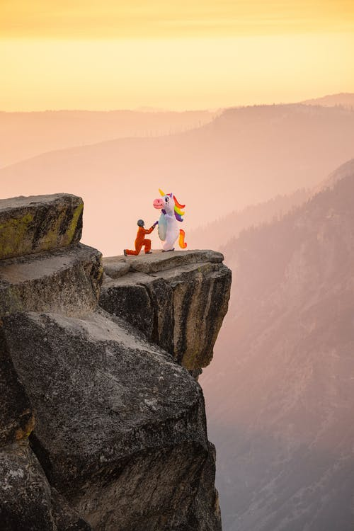 Person with Unicorn on Rocks Edge