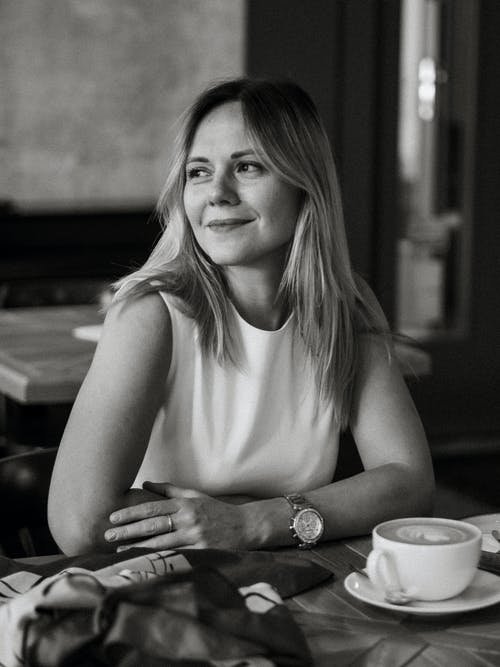 Black and White Portrait of Woman Sitting at Table Smiling