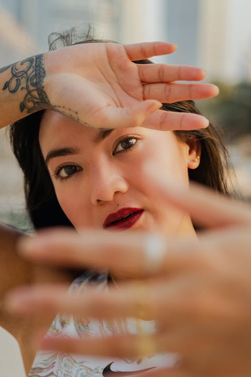 Woman with Tattoo Covering Face with Hand