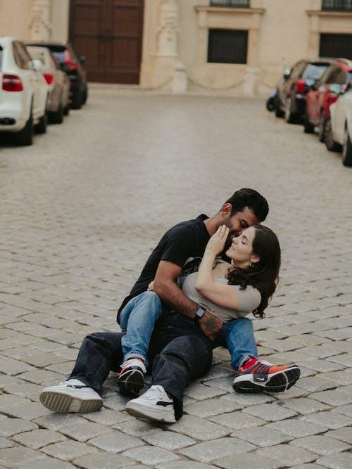 Couple Sitting on Pavement Embracing