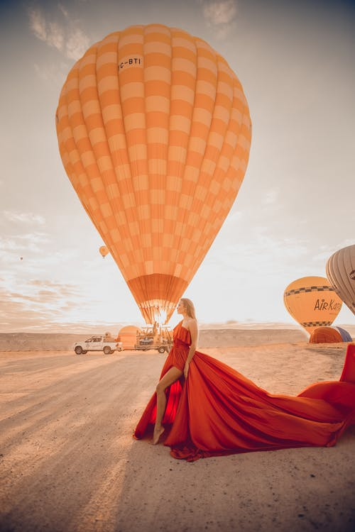 A Female Model Posing on a Desertwith A Hot AirBalloon in The Background