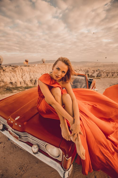 A Female Model Looking at Camera Sitting on Hood of A Car