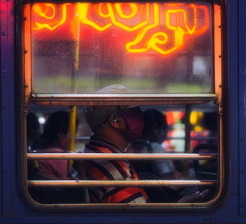 A Profile View of A Man in a Bus Waring a Face Mask