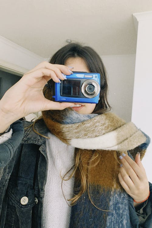 A Female Holding an AnalogCamera in Her Face