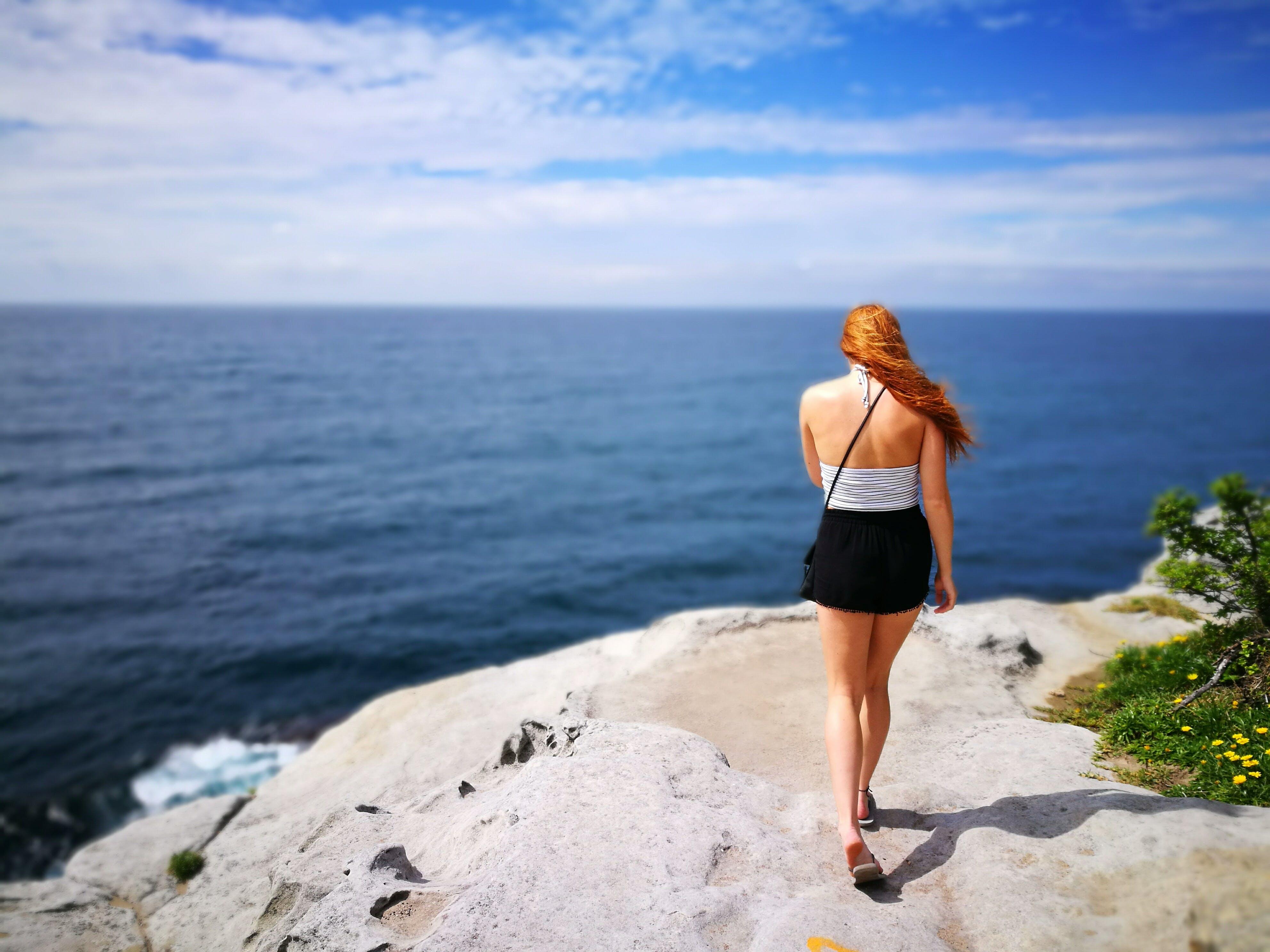 Woman Wearing Black Skirt Walking on Side of Cliff