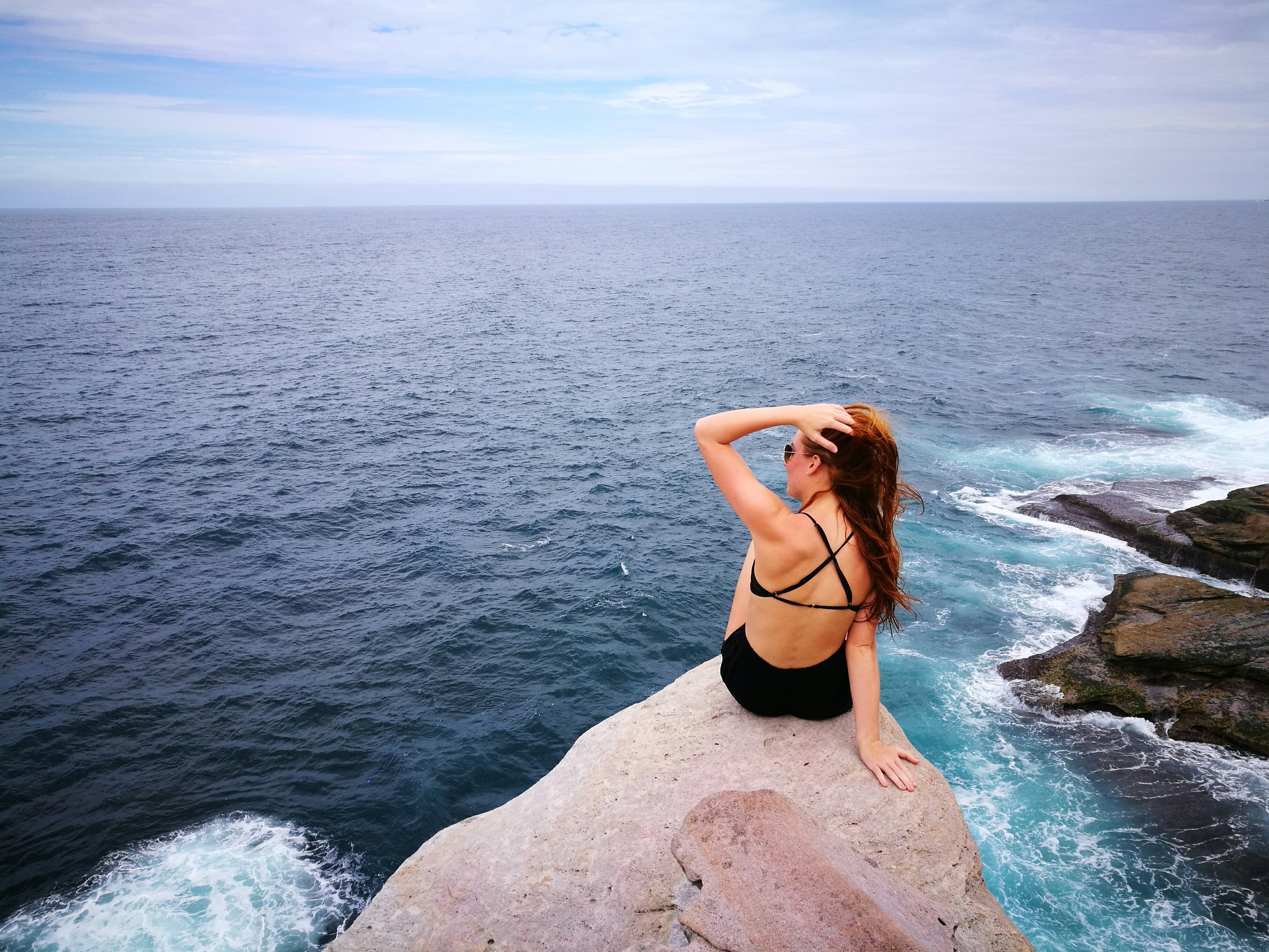 Woman in Black Swimwear Set Sitting on Top of Gray Rocky Cliff Facing Body of Water