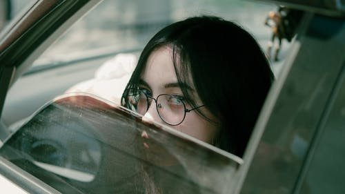 Young Woman in Glasses in Car