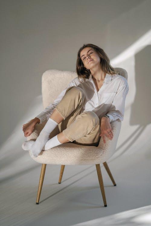 Woman in White Blazer Sitting on White Sofa Chair