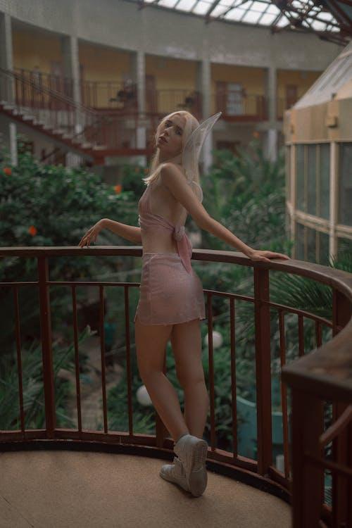 Woman in Pink Spaghetti Strap Dress Standing on Brown Wooden Bridge