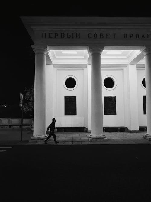 Person Passing by a Building at Night