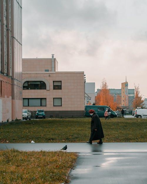 Man in Black Jacket Walking on Sidewalk Near Building