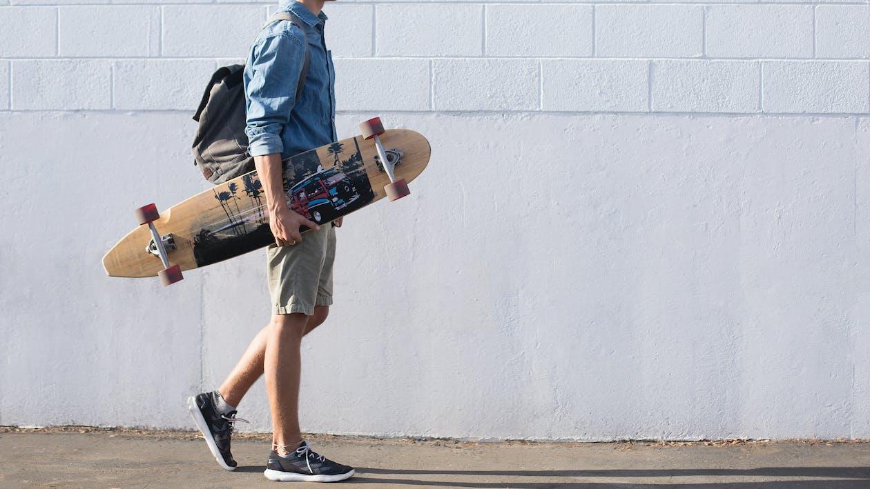 Man In Blue Top Carrying A Longboard