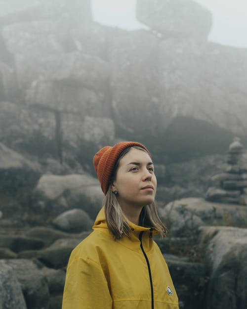 Blonde Woman Against Stones in Foggy Weather