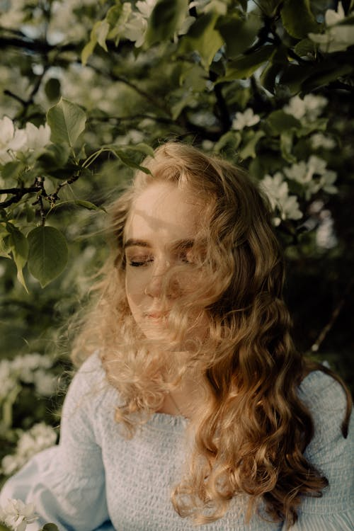 Blonde Wavy-haired Woman Among Green Leafs