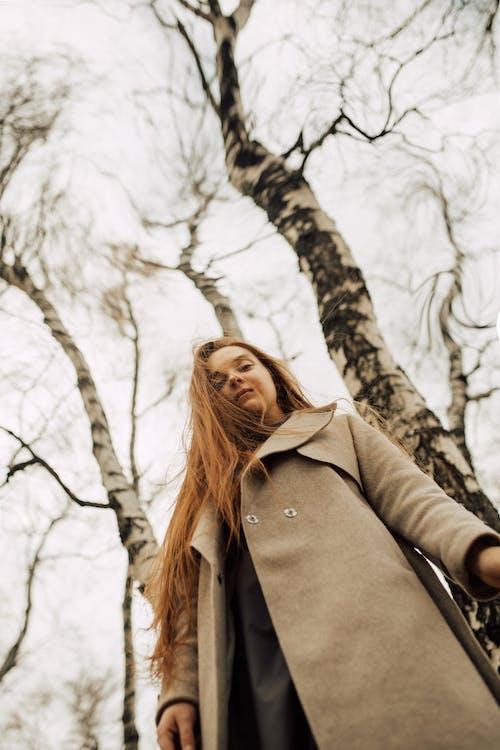 Woman in Brown Coat Standing Near Brown Tree